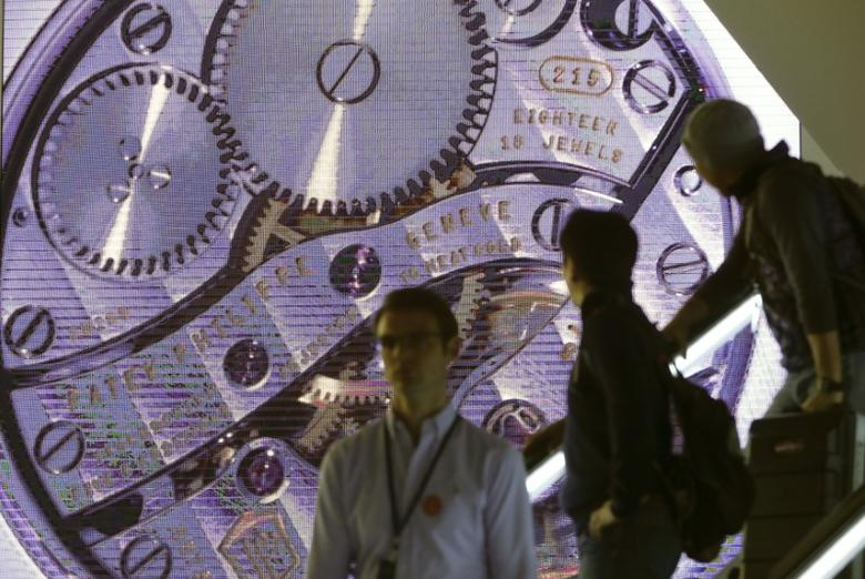 A movement of a watch of Swiss manufacturer Patek Philippe is seen on a screen behind people on a staircase at Baselworld fair in Basel March 18, 2015.  REUTERS/Arnd Wiegmann