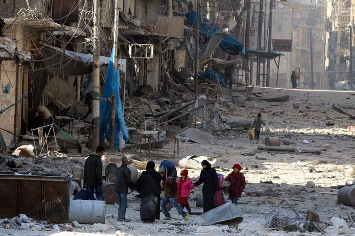 Syrians walk over rubble of damaged buildings, while carrying their belongings, as they flee clashes between government forces and rebels in Tariq al-Bab and al-Sakhour neighborhoods of eastern Aleppo towards other rebel held besieged areas of Aleppo, Syria November 28, 2016. REUTERS/Abdalrhman Ismail/Files