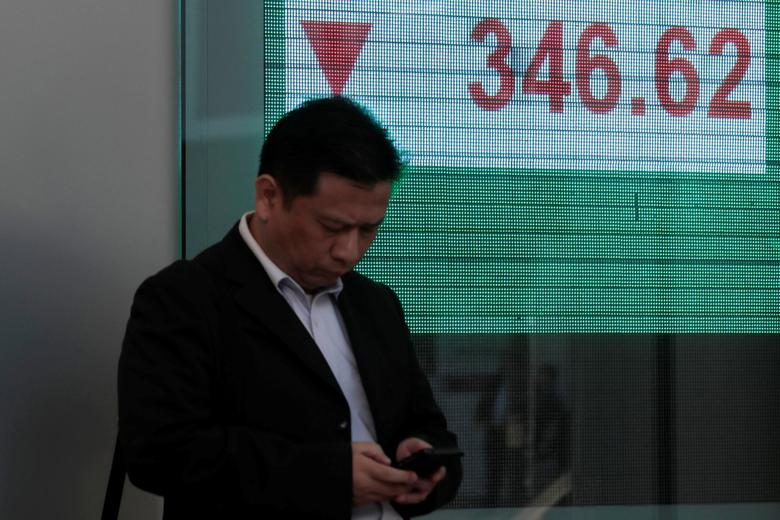 A man looks at his phone in front of a panel displaying the benchmark Hang Seng Index during morning trading in Hong Kong, China, December 15, 2016. REUTERS/Tyrone Siu