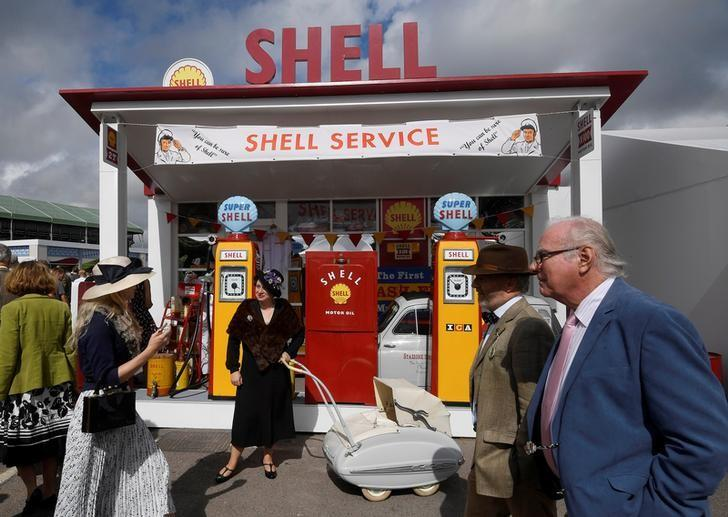 Visitors and car enthusiasts walk in front of restored Shell petrol pumps as they attend the Goodwood Revival historic motor racing festival, an annual event celebrating a mid-twentieth century heyday of the racing circuit, near Chichester, Britain. REUTERS/Toby Melville