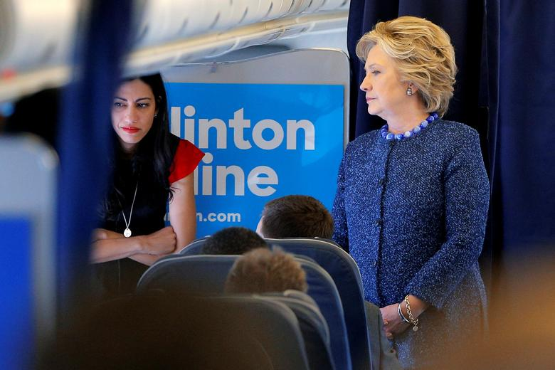 U.S. Democratic presidential nominee Hillary Clinton talks to staff members, including aide Huma Abedin (L), onboard her campaign plane in White Plains, New York, U.S. October 28, 2016.  REUTERS/Brian Snyder