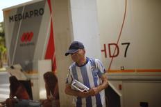 Grupos de inversores asiáticos, europeos y americanos han presentado esta semana alrededor de diez ofertas no vinculantes para tomar una participación en el grupo español de gestión de derechos audiovisuales Imagina, dijeron el miércoles dos fuentes conocedoras de la operación. En la imagen, un aficionado del Málaga escucha la radio cerca de un autobús de Mediapro antes de un partido amistoso entre el Málaga y el Everton en el exterior del estadio de La Rosaleda, Málaga, 11 de agosto de 2012. REUTERS/Jon Nazca