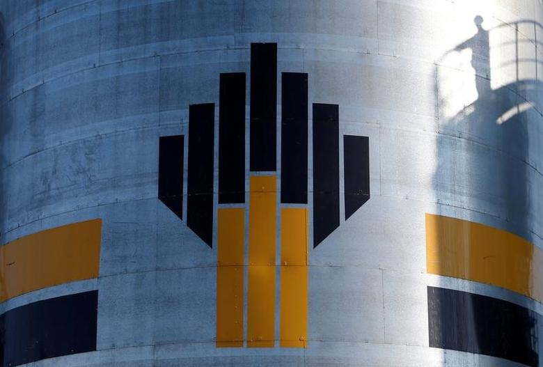 The shadow of a worker is seen next to a logo of Russia's Rosneft oil company at the central processing facility of the Rosneft-owned Priobskoye oil field outside the West Siberian city of Nefteyugansk, Russia, August 4, 2016. REUTERS/Sergei Karpukhin/Files