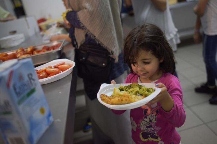 Migrants get food for the Iftar (breaking fast) meal at a refugee shelter in a former hotel in Berlin, Germany June 9, 2016. REUTERS/Stefanie Loos