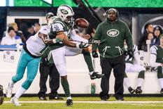 Dec 17, 2016; East Rutherford, NJ, USA; New York Jets cornerback Juston Burris (32) intercepts a pass from Miami Dolphins quarterback Matt Moore (not pictured) in the third quarter and is tackled by Dolphins wide receiver Jarvis Landry (14) at MetLife Stadium. Mandatory Credit: Dennis Schneidler-USA TODAY Sports