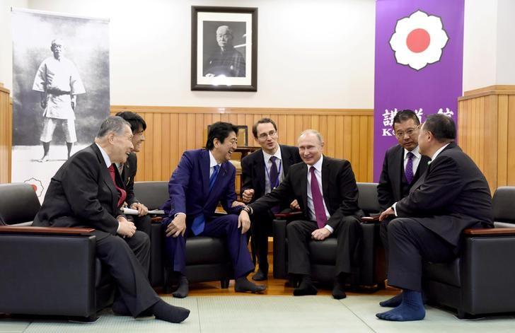 Russian President Vladimir Putin (3rd R) chats with Japanese Prime Minister Shinzo Abe (3rd L), former Japanese Prime Minister Yoshiro Mori (L) and Vice Chairman of the All Japan Judo Federation Yasuhiro Yamashita (R) when they visit the Kodokan Judo Institute, the headquarters of the worldwide judo community, in Tokyo on December 16, 2016.  REUTERS/Toru Yamanaka/Pool