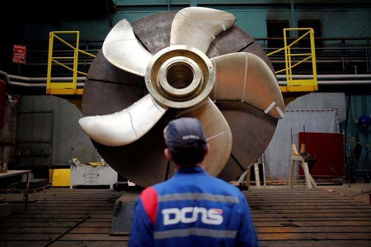 An employee looks at the propeller of a Scorpene submarine at the industrial site of the naval defence company and shipbuilder DCNS in La Montagne near Nantes, France, April 26, 2016. REUTERS/Stephane Mahe/File Photo