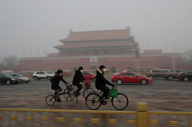 People wearing masks cycle past Tiananmen Gate during the smog after a red alert was issued for heavy air pollution in Beijing, China, December 20, 2016. REUTERS/Jason Lee