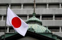 Японский флаг над зданием Банка Японии в Токио. Банк Японии во вторник оставил монетарную политику без изменений и выразил более оптимистичный, чем раньше, взгляд на экономику, усилив ожидания рынка относительно того, что в будущем регулятор может пойти на повышение, а не понижение процентных ставок. REUTERS/Toru Hanai/File Photo