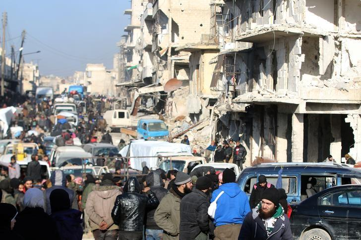Rebel fighters and civilians wait near damaged buildings to be evacuated from a rebel-held sector of eastern Aleppo, Syria December 18, 2016.  REUTERS/Abdalrhman Ismail