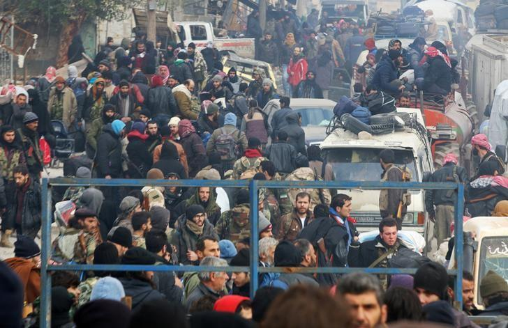 Rebel fighters and civilians gather as they wait to be evacuated from a rebel-held sector of eastern Aleppo, Syria December 16, 2016. REUTERS/Abdalrhman Ismail/File Photo