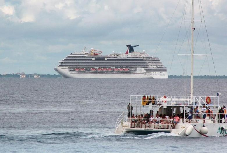 Tourists enjoy a ride on a catamaran as cruise ship Carnival Magic is seen near the shores of Cozumel October 17, 2014. REUTERS/Stringer