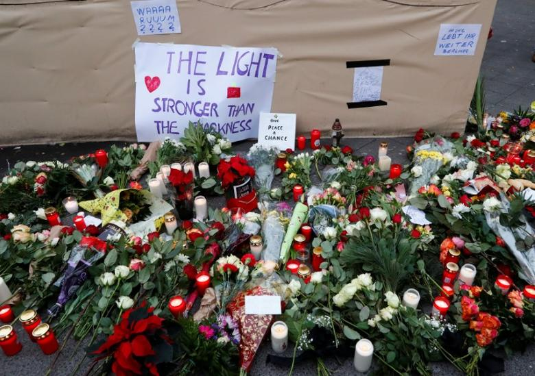 Flowers and posters are placed at the scene where a truck ploughed into a crowded Christmas market in the German capital last night in Berlin, Germany, December 20, 2016 REUTERS/Fabrizio Bensch