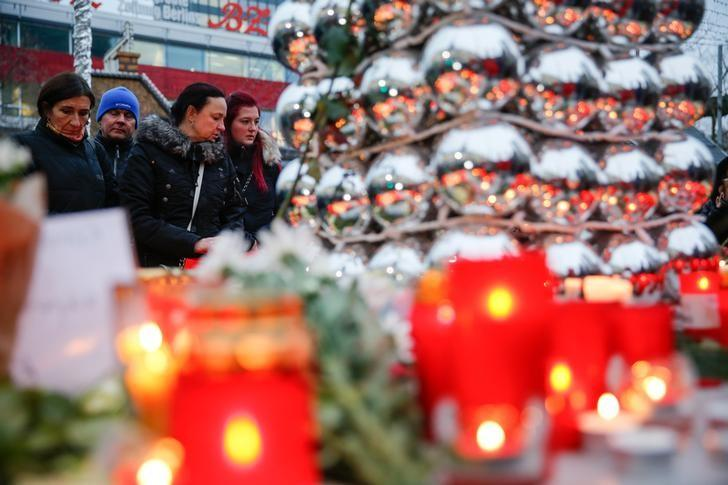 Mourners look at candles and Christmas tree balls at the Christmas market in Berlin, Germany, December 20, 2016, one day after a truck ploughed into a crowded Christmas market in the German capital.       REUTERS/Hannibal Hanschke