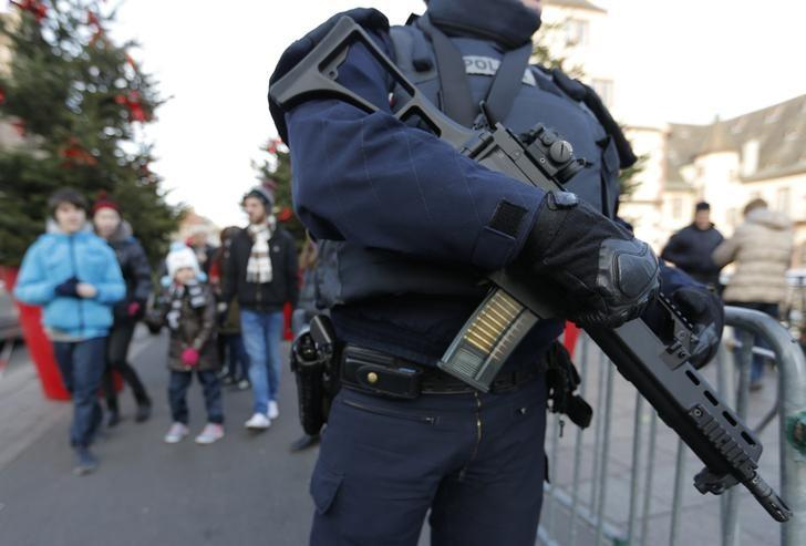 An armed French policeman stands guard as tourists visit the traditional Christkindelsmaerik (Christ Child market) as emergency security measures continue during the Christmas holiday season in Strasbourg, France, December 20, 2016. REUTERS/Vincent Kessler