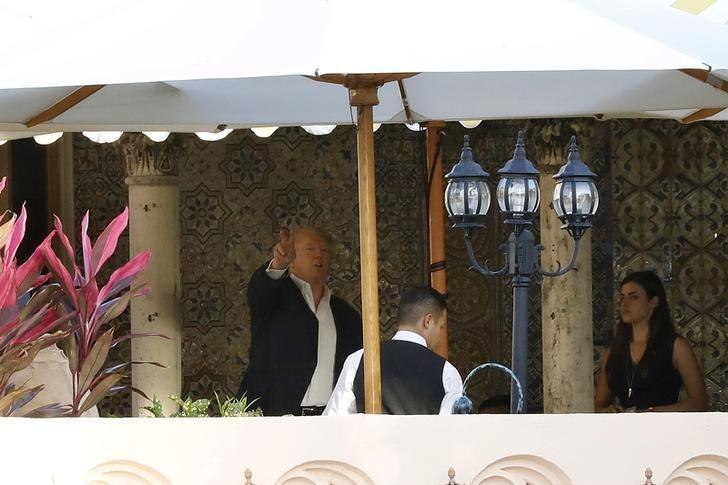 U.S. President-elect Donald Trump (L) gestures as he stands on a balcony at the Mar-a-Lago estate in Palm Beach, Florida, U.S., December 19, 2016. REUTERS/Lucas Jackson