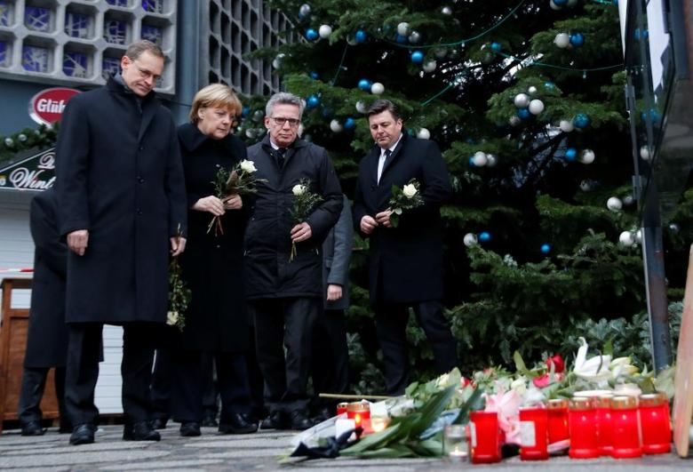 Berlin mayor Michael Mueller, German Chancellor Angela Merkel and Interior Minister Thomas de Maiziere prepare to lay flowers at the Christmas market in Berlin, Germany, December 20, 2016, where a truck ploughed into the crowd on Monday.        REUTERS/Hannibal Hanschke