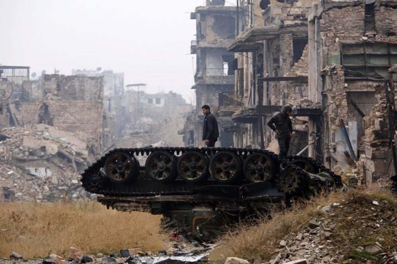 FILE PHOTO: Forces loyal to Syria's President Bashar al-Assad stand atop a damaged tank near Umayyad mosque, in the government-controlled area of Aleppo, during a media tour, Syria December 13, 2016. REUTERS/Omar Sanadiki/File Photo