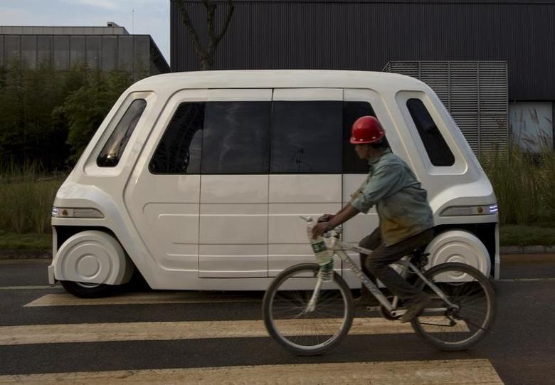 A worker rides a bike past a driverless vehicle at Vanke's Building Research Centre testing area in Dongguan, south China's Guangdong province November 2, 2015.  REUTERS/Tyrone Siu/Files