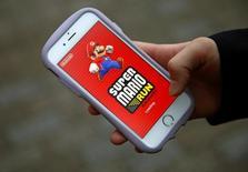 """Takuya Nishya muestra el juego """"Super Mario Run"""", de Nintendo en la pantalla de su teléfono móvil en Tokio, dic 20, 2016. El primer título del juego Mario de Nintendo Co Ltd para teléfonos inteligentes alcanzó un récord de descargas pero los usuarios se mostraron reacios ante el costo único para desbloquear contenido, lo que llevó a las acciones del fabricante japonés de videojuegos a mínimos de un mes.    REUTERS/Kim Kyung-Hoon"""