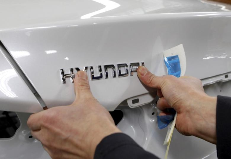 A worker fixes the Hyundai logo on a vehicle at a plant of Hyundai Motor in Asan, south of Seoul, February 9, 2012.  REUTERS/Lee Jae-Won/File Photo - RTX2V5PH
