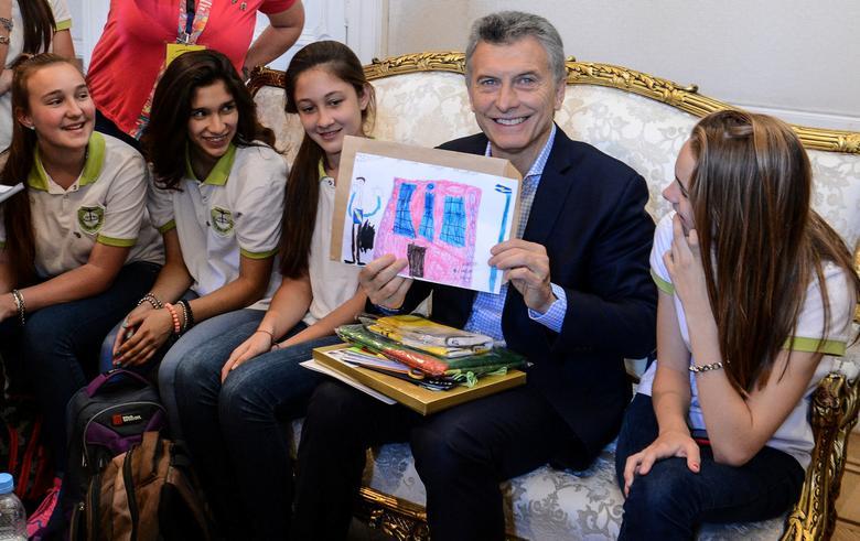 Argentine President Mauricio Macri shows a drawing as he visits the Juan Bautista Alberdi School in Elisa, Argentina December 15, 2016. Argentine Presidency/Handout via REUTERS