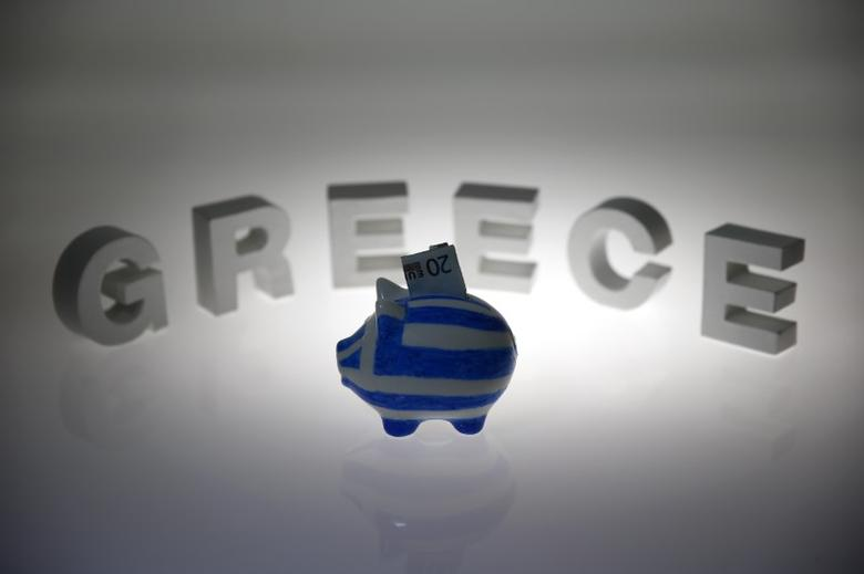 A piggybank painted in the colours of the Greek flag with a 20 euro banknote in it's slot, stands in front of letters spelling the word 'GREECE' in this picture illustration taken in Berlin, Germany June 30, 2015. REUTERS/Pawel Kopczynski  - RTX1IDZ2