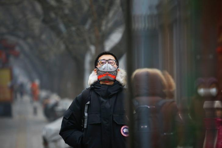 Designer Wang Zhijun poses for pictures wearing one of the face masks he made using sneakers, in Beijing, China December 21, 2016. REUTERS/Damir Sagolj