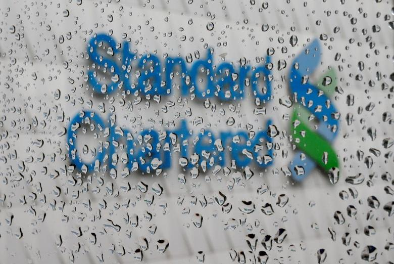 A Standard Chartered logo at its headquarters is seen through a window with raindrops, in Hong Kong, China August 4, 2016. REUTERS/Tyrone Siu/File Photo