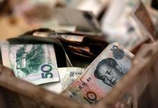 Monedas chinas en la caja de un vendedor en Pekín. 14 de febrero de 2014.China podría ajustar sus inversiones en bonos del Tesoro de Estados Unidos ya que una disminución de sus tendencias de deuda puede considerarse como una medida táctica, dijo a periodistas el jueves Li Hongyan, un funcionario de regulación del mercado de divisas. REUTERS/Kim Kyung-Hoon