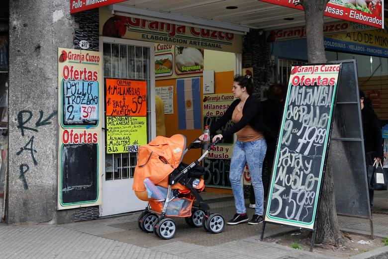 A woman pushing a baby carriage walks past a shop selling farm products in Buenos Aires July 31, 2014.    REUTERS/Enrique Marcarian