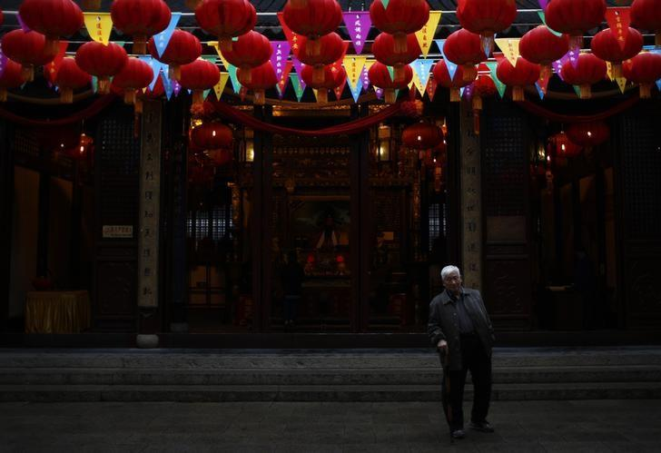 A man walks under Chinese New Year decorations as he visit the Old City God Temple in Yuyuan Garden in Shanghai January 29, 2014. REUTERS/Carlos Barria