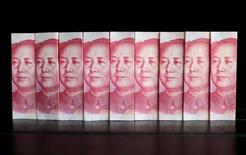 En la imagen, billetes de 100 yuanes chinos en una foto tomada en Pekín, 11 de julio de 2013. Los líderes de China han manifestado que el crecimiento se ralentizará levemente en el 2017, dijeron asesores de política, en momentos en que buscan un equilibrio entre el apoyo a la economía con unas condiciones laxas de crédito y la prevención de una acumulación desestabilizadora de endeudamiento. REUTERS/Jason Lee/File Photo