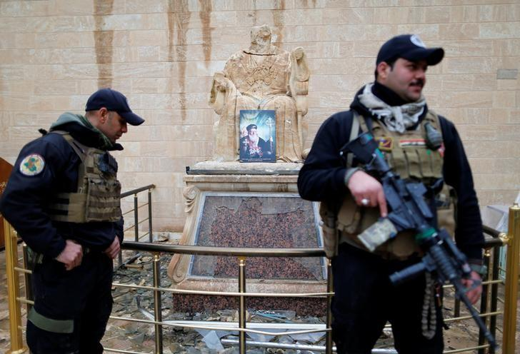 Security members stand guard during a mass on Christmas Eve at the Mar Shemoni church in the town of Bartella east of Mosul, December 24, 2016. REUTERS/Ammar Awad