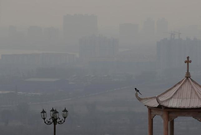 12月24日、中国の保健当局高官は23日、同国北部で続くスモッグが健康に与える影響を調べるため、全国の126カ所に監視地点を置くことを明らかにした。写真は厚いスモッグに覆われている町の様子。山西省清徐県で撮影(2016年 ロイター/Jason Lee)