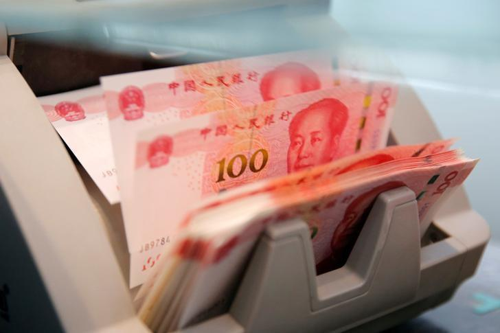 FILE PHOTO: Chinese 100 yuan banknotes are seen in a counting machine while a clerk counts them at a branch of a commercial bank in Beijing, China, March 30, 2016. REUTERS/Kim Kyung-Hoon/File Photo
