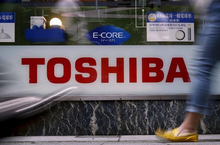 Pedestrians walk past a logo of Toshiba Corp outside an electronics retailer in Tokyo, Japan, June 25, 2015. REUTERS/Yuya Shino/Files