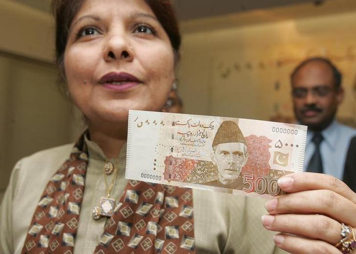 Pakistan State Bank governor Shamshad Akhtar holds a 5,000 rupees ($83) currency note during a news briefing in Karachi May 26, 2006. REUTERS/Athar Hussain/Files