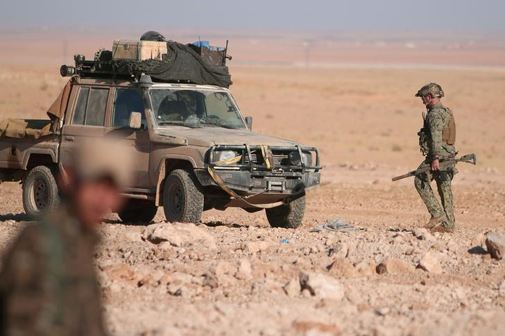 A U.S. fighter walks with his weapon near a military vehicle, north of Raqqa city, Syria November 6, 2016. REUTERS/Rodi Said/Files