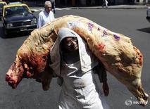 Imagen de archivo del carnicero Hugo Ruiz Díaz descargando carne de un camión junto a su tienda en Buenos Aires. 9 febrero 2006. Las exportaciones de carne vacuna de Argentina crecieron un 10 por ciento interanual entre enero y octubre, a 193.000 toneladas, dijo el martes el Gobierno del país austral, que hace un año eliminó las restricciones y un impuesto que regían sobre los embarques del alimento. REUTERS/Marcos Brindicci