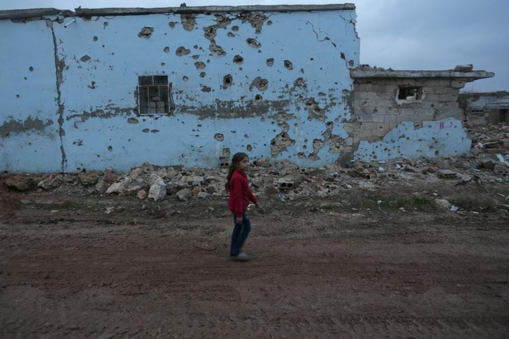 A girl walks near a damaged house in al-Rai town, northern Aleppo province, Syria December 27, 2016. REUTERS/Khalil Ashawi