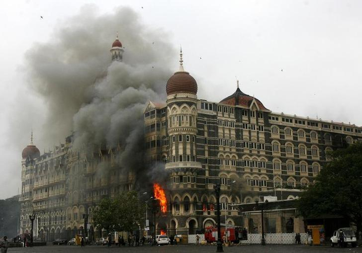The Taj Mahal hotel is seen engulfed in smoke during a gun battle in Mumbai November 29, 2008. REUTERS/Arko Datta/File Photo