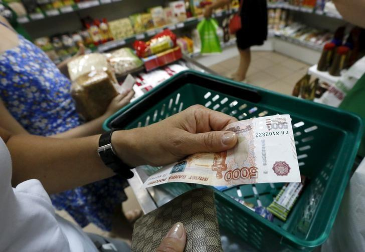 A customer holds a Russian 5,000-rouble as she buys food at a grocery shop in the Siberian city of Krasnoyarsk, Russia, August 6, 2015. REUTERS/Ilya Naymushin