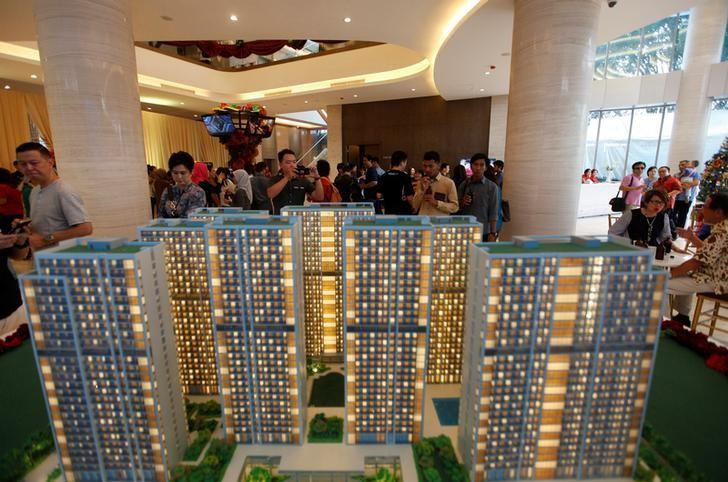 Visitors look at a model of Daan Mogot City apartment development, a residential project planned by a unit of China Communication Construction Group (CCCG), inside the sales office on opening day in Cengkareng, West Jakarta, Indonesia December 10, 2016. Picture taken December 10, 2016.  REUTERS/Fatima El-Kareem