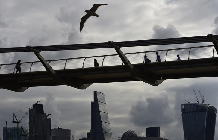 Workers cross the Millenium Bridge with the City of London seen behind, in London July 30, 2014. REUTERS/Toby Melville