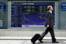 Un hombre pasa por delante de una tabla electrónica que muestra el promedio del Nikkei fuera de una correduría en Tokio, Japón, 1 de abril 2016.El promedio de acciones japonés Nikkei cayó a un mínimo de tres semanas el viernes en una sesión volátil debido a que los inversores tomaron ganancias en el último día hábil de 2016, pero el mercado logró registrar ganancias marginales para el año. REUTERS/Thomas Peter - RTSD3HP