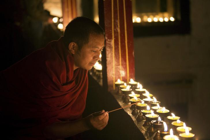 A Tibetan monk lights butter lamps to celebrate the Butter Lamp Festival at the Ramoche Temple in Lhasa, Tibet Autonomous Region, China, December 5, 2015. The annual Butter Lamp Festival falls on the 25th day of the 10th month of the Tibetan calendar every year in commemoration of Tsong Khapa, the founder of the Gelug sect of Tibetan Buddhism. Picture taken December 5, 2015. REUTERS/Stringer CHINA OUT. NO COMMERCIAL OR EDITORIAL SALES IN CHINA