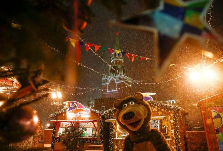 FILE PHOTO: A street performer dressed as a bear is seen at a Christmas and New Year market, with the Kremlin's Spasskaya Tower seen in the background, at the Red Square in Moscow, Russia, December 5, 2016. REUTERS/Maxim Shemetov/File Photo