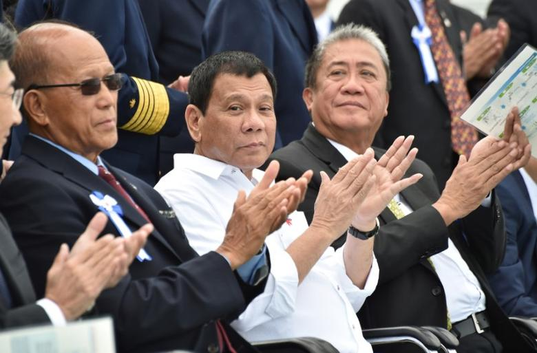 Philippine President Rodrigo Duterte (C), accompanied by Transportation Secretary Arthur Tugade (R) and Defense Secretary Delfin N Lorenzana (L), claps at the end of Japan's coast guard drills in Yokohama, Japan October 27, 2016. REUTERS/Kazuhiro Nogi/Pool