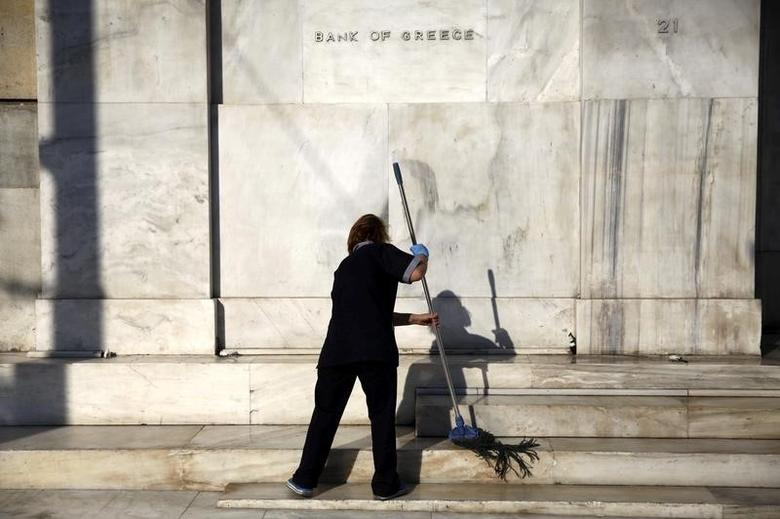 A cleaning lady mops the steps at the main entrance of the Bank of Greece headquarters in Athens, Greece, July 15, 2015.    REUTERS/Yiannis Kourtoglou/File Photo